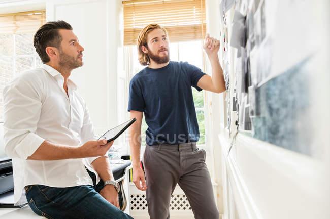 Young male designer explaining — Stock Photo