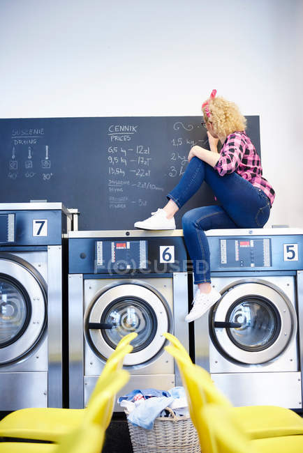 Laundrette owner sitting on top of washing machine — Stock Photo