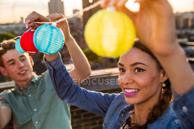 Man and woman hanging lights — Stock Photo