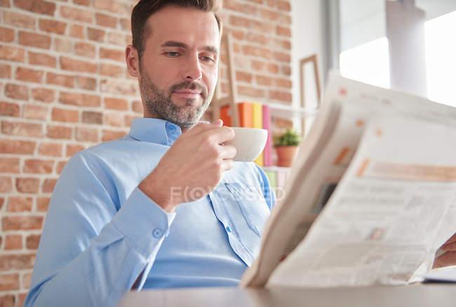 Uomo leggendo giornale bere caffè — Foto stock