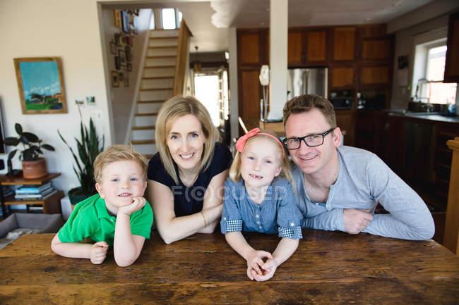 Pais na mesa de cozinha com crianças — Fotografia de Stock