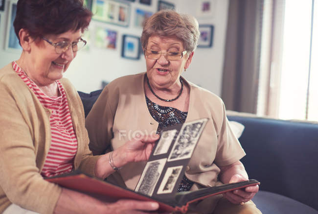 Women on sofa looking at old photograph — Stock Photo