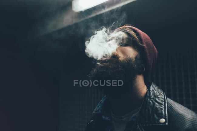 Хипстер в вязаной шляпе, курящий ночью — стоковое фото