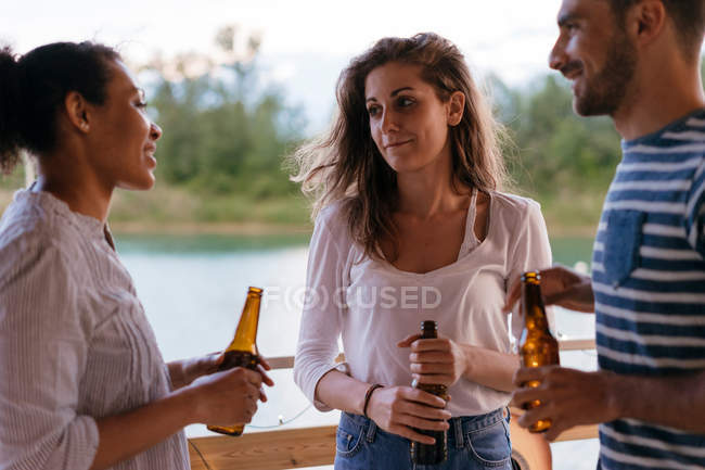Drei Freunde halten Flaschen Bier — Stockfoto