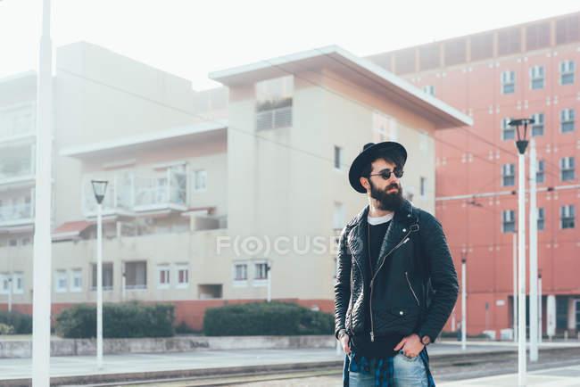 Hipster esperando en la estación de tranvía de la ciudad - foto de stock