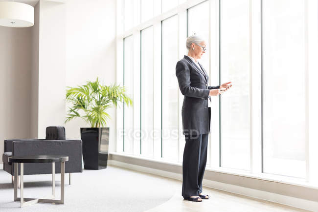 Mature businesswoman looking at smartphone — Stock Photo