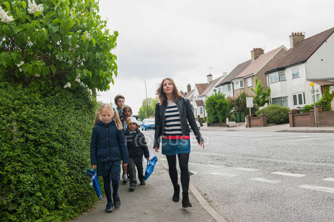 Childminder walking children to school — Stock Photo