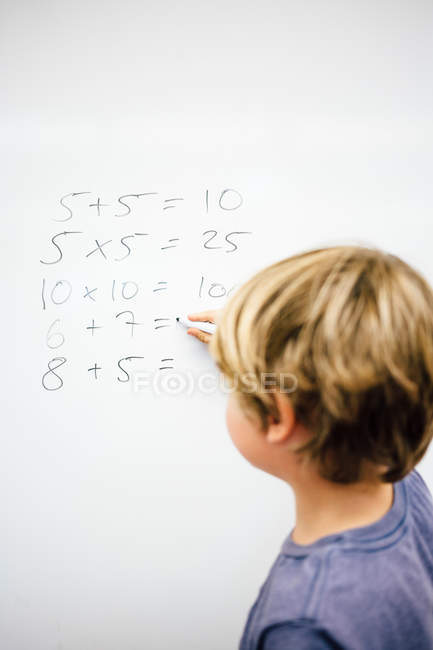 Boy doing sums on whiteboard — Stock Photo