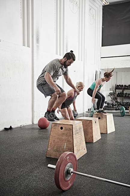 Friends jumping onto fitness boxes — Stock Photo