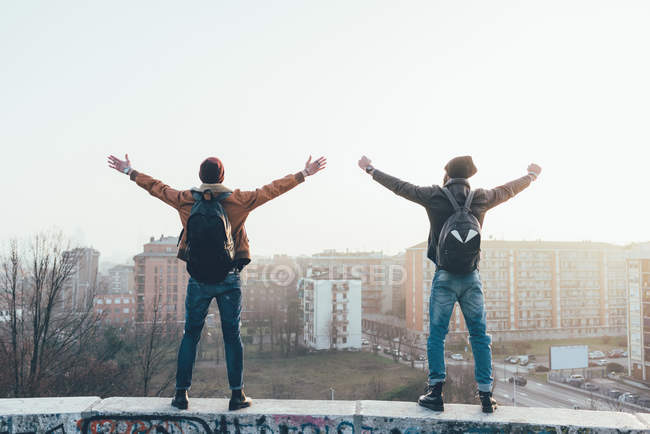 Male hipsters standing on city wall with arms out — Stock Photo