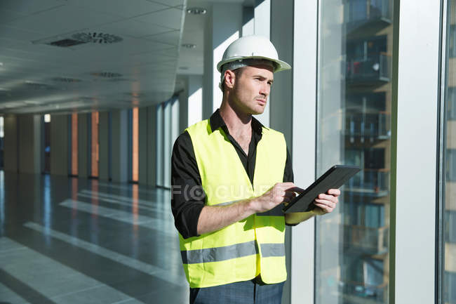 Man wearing hard hat and hi vis vest — Stock Photo