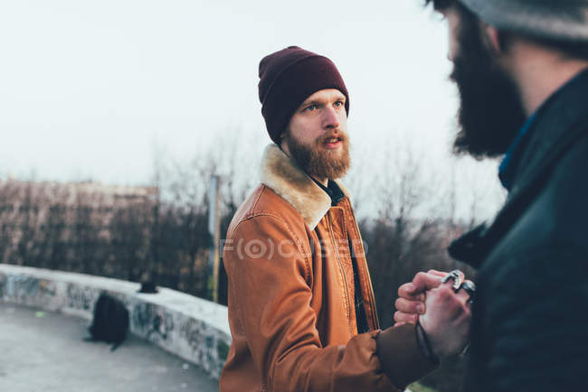 Male hipsters fist bumping in park — Stock Photo