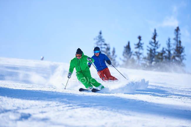 Двое мужчин лыжах вниз — стоковое фото