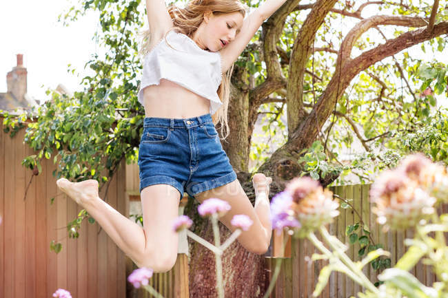 Teenage girl jumping in air — Stock Photo