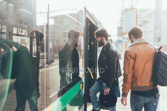 Young men boarding tram — Stock Photo