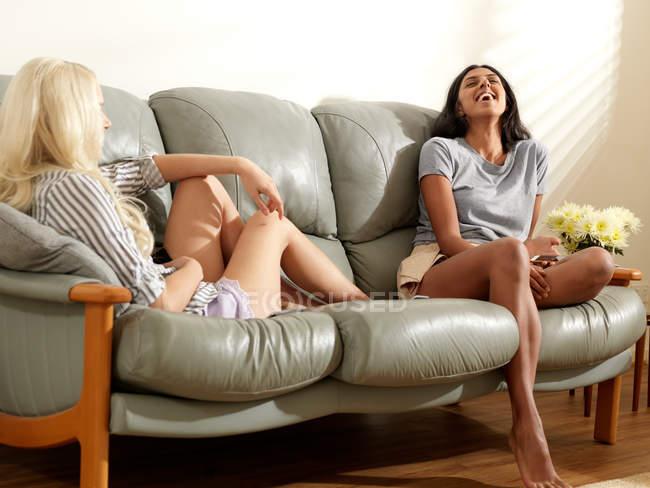 Amigos sentados en el sofá y riendo - foto de stock