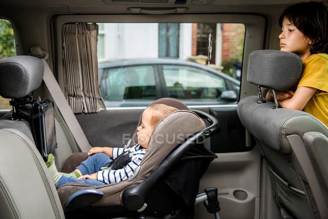 Bebê e irmão mais velho no carro — Fotografia de Stock