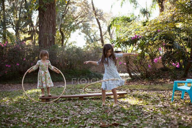 Сестри, граючи з пластикових обручі — стокове фото