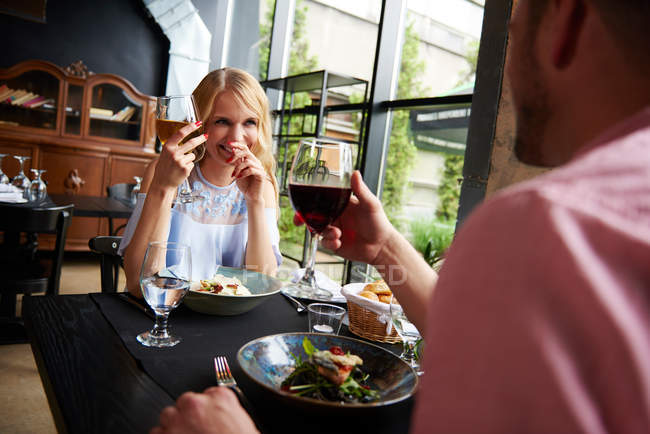 Young woman with boyfriend at restaurant — Stock Photo