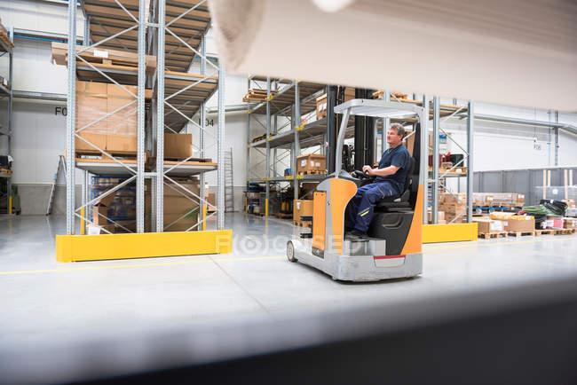 Hombre conduciendo montacargas en almacén de distribución - foto de stock