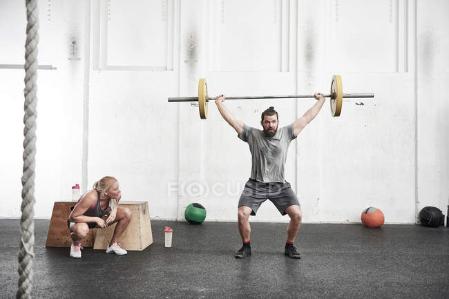 Man lifting barbell in gym — Stock Photo