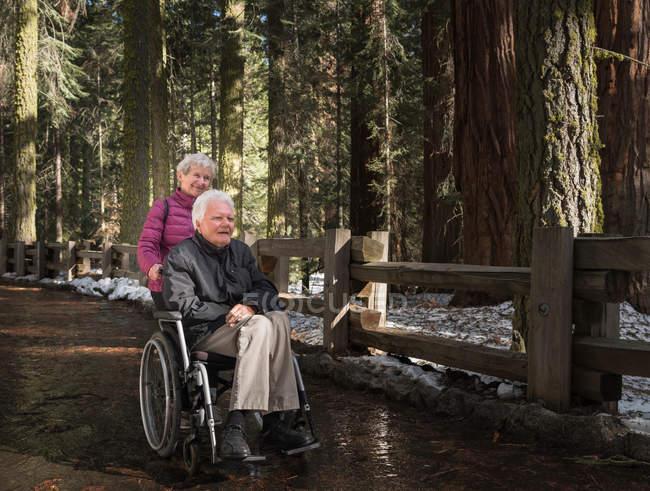 Senior mulher empurrando marido em cadeira de rodas — Fotografia de Stock