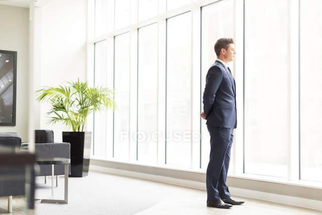 Selbstbewusster Geschäftsmann blickt durchs Fenster — Stockfoto