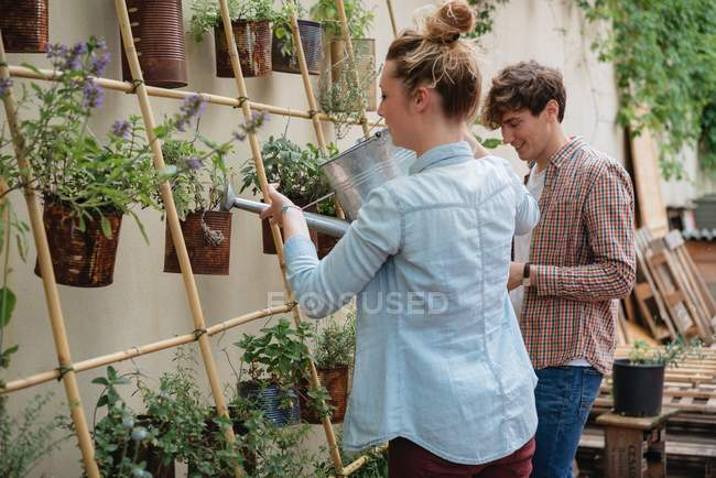 Man and woman tending to plants growing in cans — Stock Photo