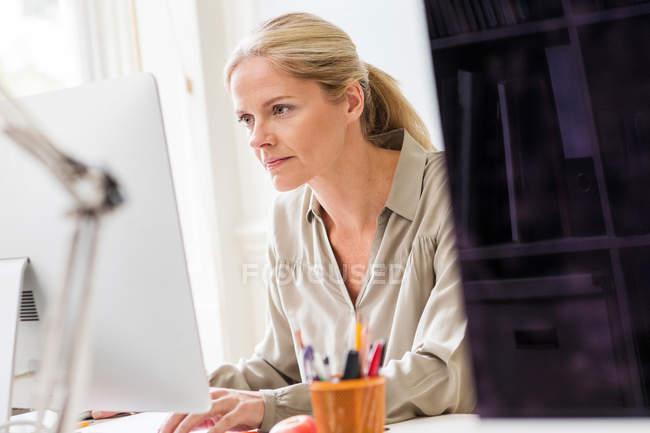 Designer typing at desktop computer — Stock Photo