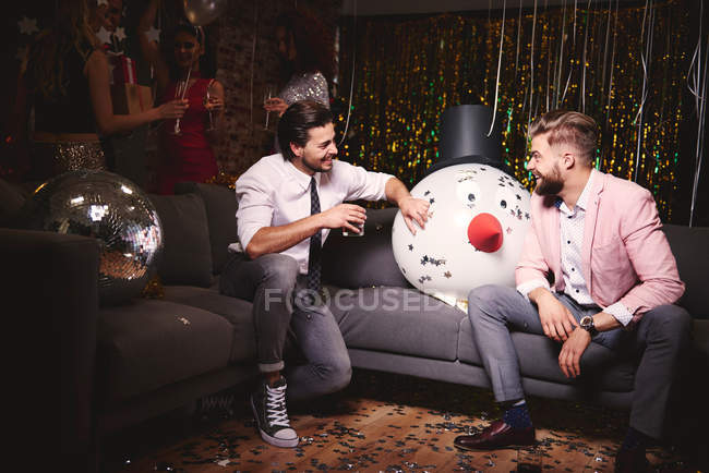 Men sitting on sofa at party — Stock Photo
