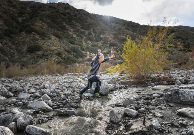 Chico saltando sobre rocas - foto de stock