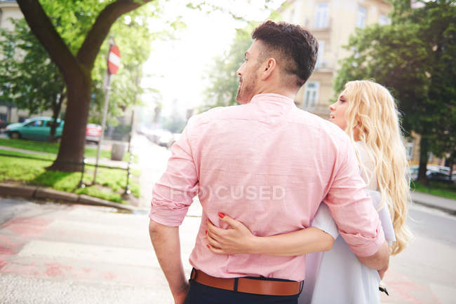 Couple walking arms around each other — Stock Photo