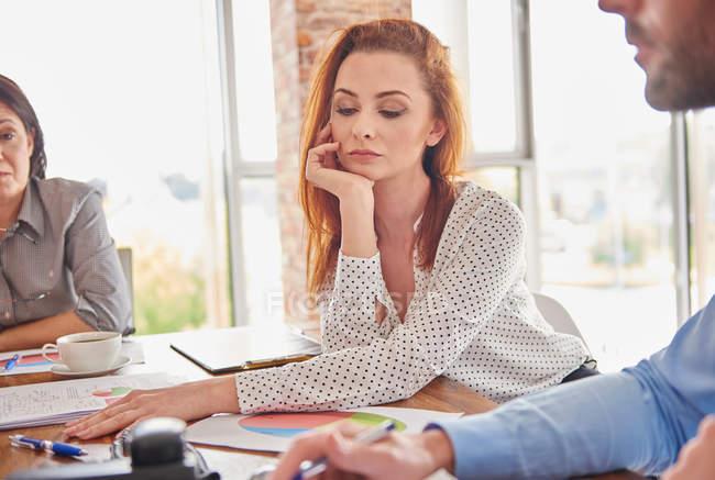 Donna di affari nella riunione la mano sul mento — Foto stock