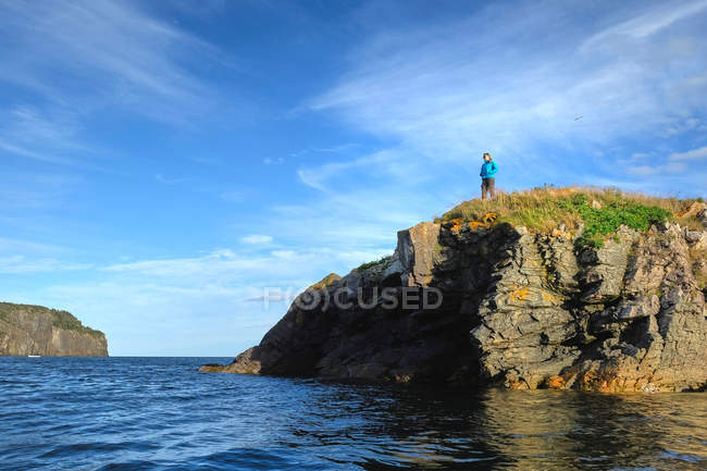 Woman looking out from coastal cliff — Stock Photo