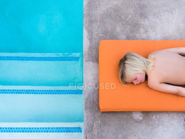 Ragazzo sdraiato a bordo piscina — Foto stock