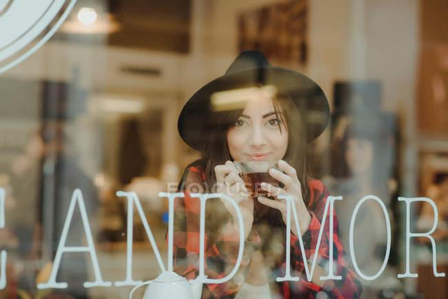 Молодая женщина сидит в кафе — стоковое фото