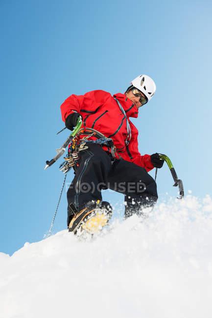Homem adulto médio escalando na neve — Fotografia de Stock