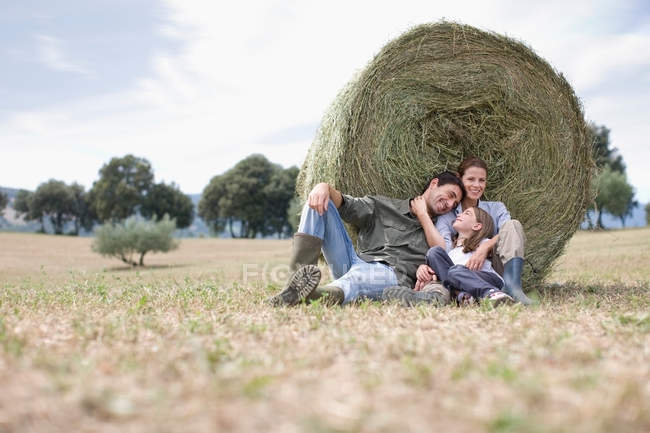 Parents and daughter sitting in field — Stock Photo
