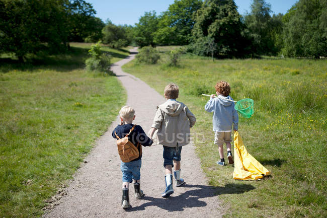Three boys walking on dirt road — Stock Photo