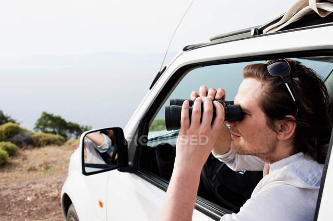 Hombre en el coche mirando a través de binoculares - foto de stock