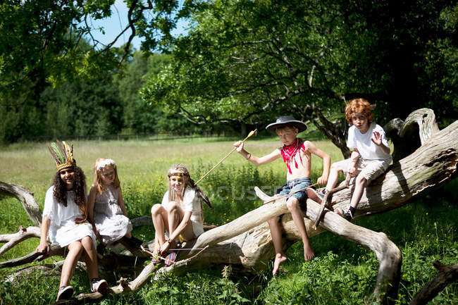 Children in costumes sitting on tree trunk — Stock Photo