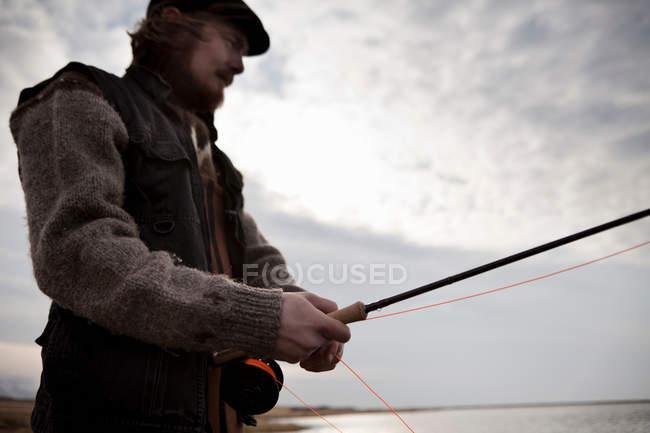 Homme utilisant la canne à pêche — Photo de stock