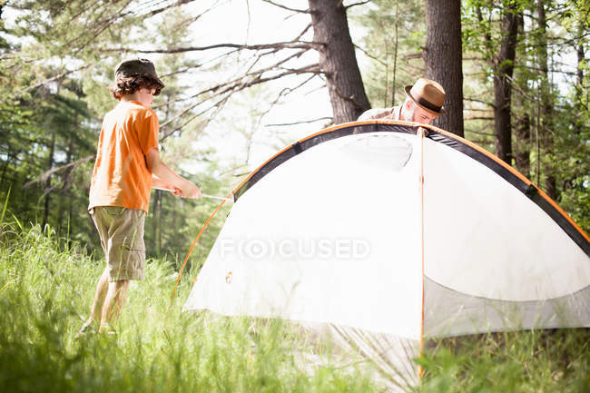 Father and son pitching tent — Stock Photo