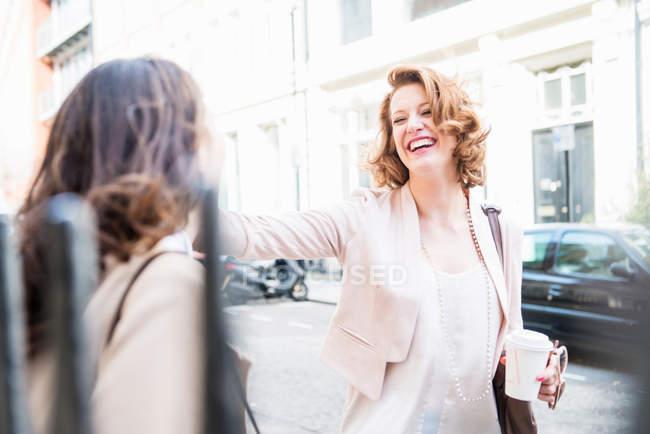 Two women laughing at street — Stock Photo