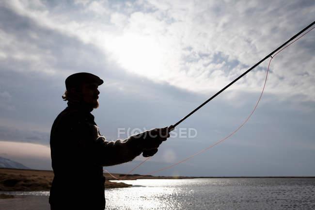 Homme pêche dans encore lac — Photo de stock