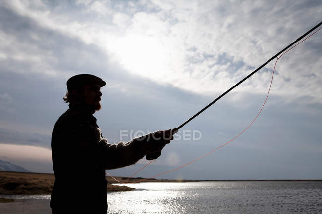 Man fishing in still lake — Stock Photo