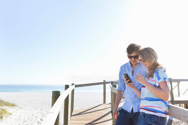 Couple on boardwalk using cell phone — Stock Photo