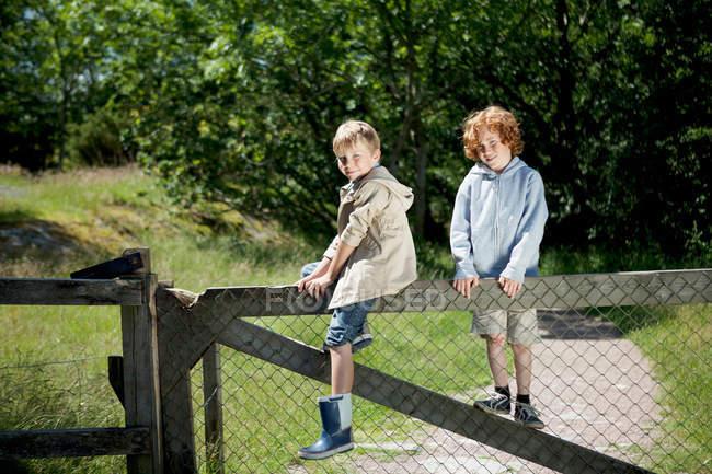 Zwei Jungen klettern auf Holzzaun — Stockfoto
