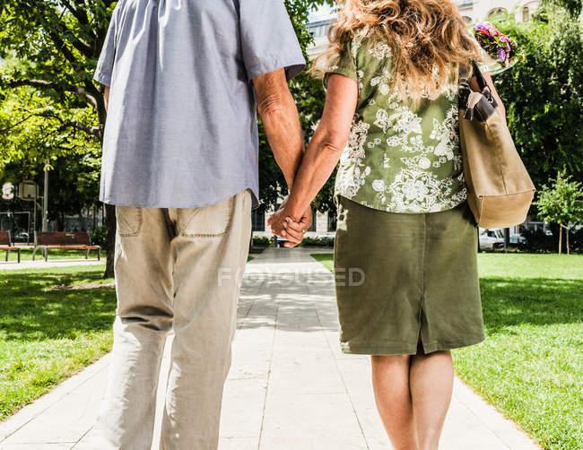 Пара, держащаяся за руки в парке — стоковое фото