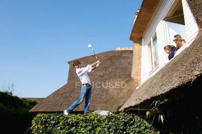 Хлопчика грати в гольф на даху — стокове фото